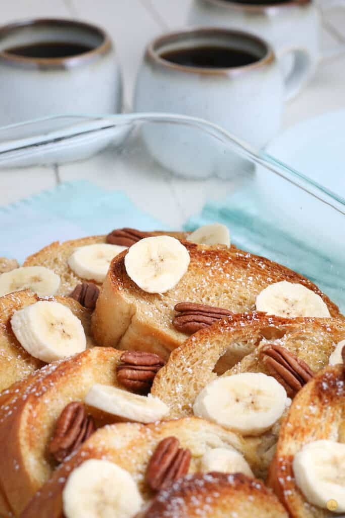 banana pecan oven baked french toast in a clear dish with two cups of coffee
