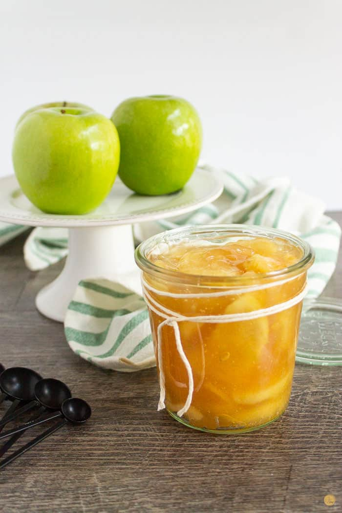 jar of apple pie filling with a cake stand and three apples