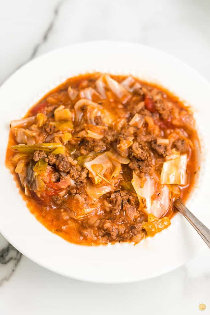 white bowl with cabbage soup and spoon