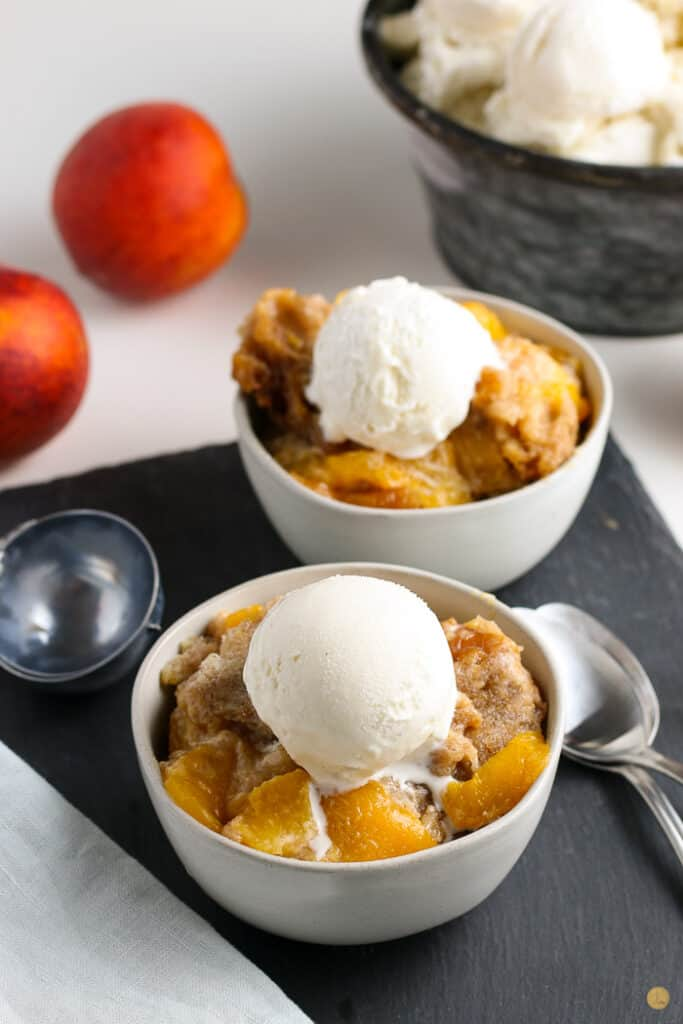 two bowls of crock pot cobbler topped with vanilla ice cream