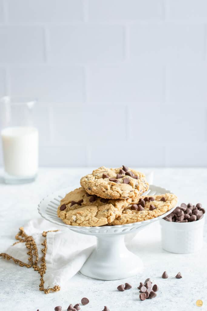 cookies on a white pie plate with milk in the background