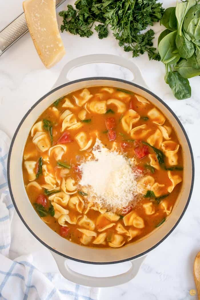 tuscan tortellini soup in pot with cheese