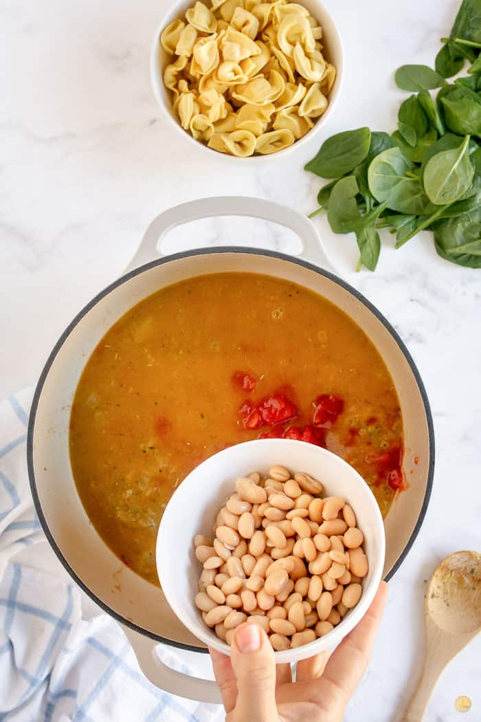beans and tomatoes being added to soup pot