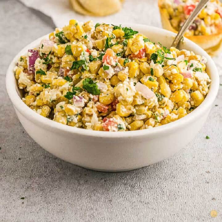 square photo of corn salad in a white bowl