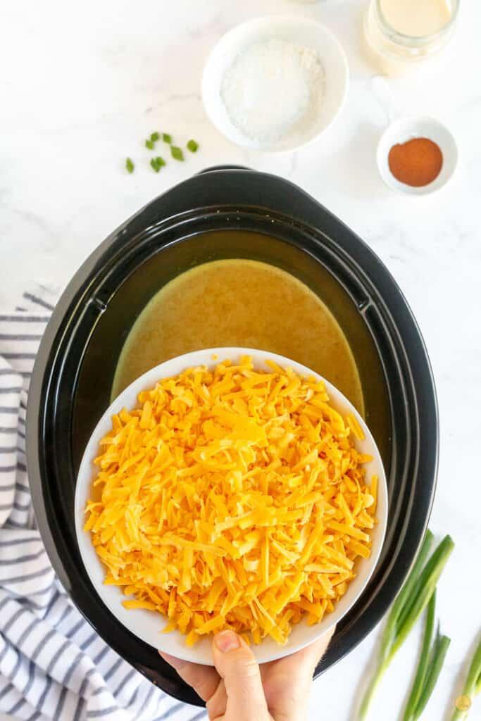 bowl of shredded cheddar over slow cooker