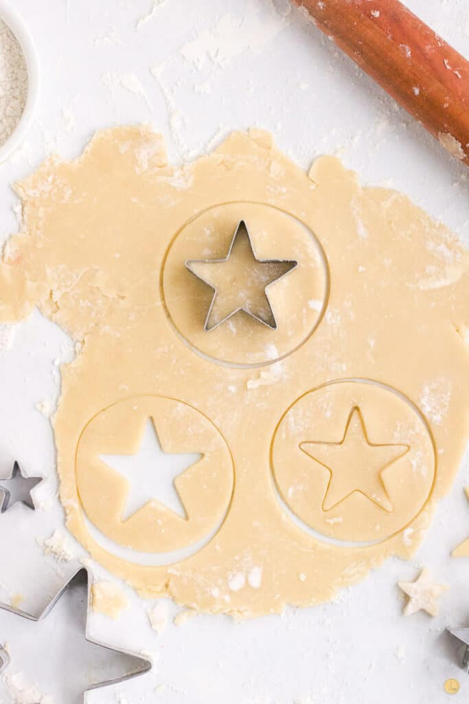 sugar cookies being cut out on a baking pan