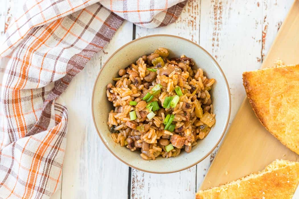 hoppin john in a white bowl with bread