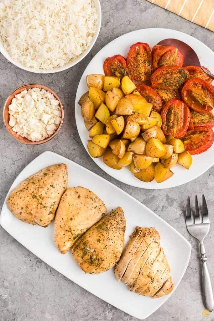 cooked chicken and tomatoes on platters