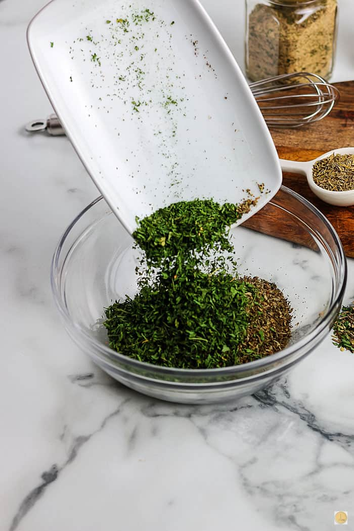 green herbs pouring into a bowl