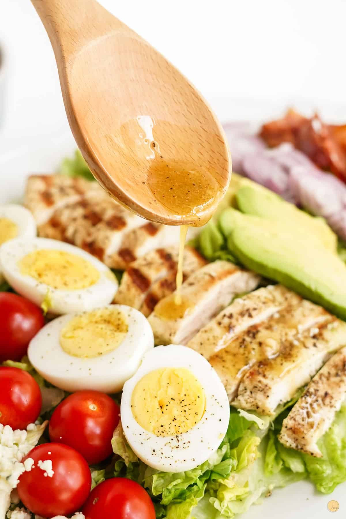 spoon drizzling salad dressing on eggs