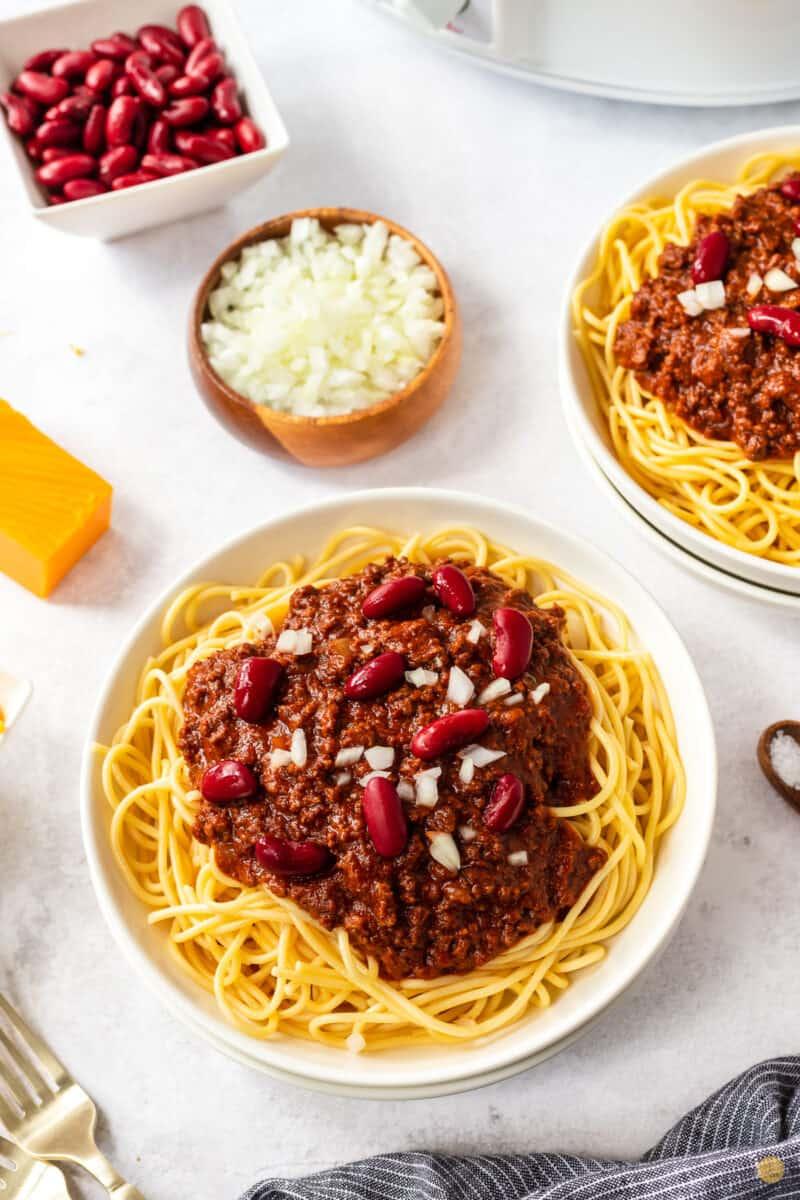 bowl of chili, spaghetti, beans, and onion