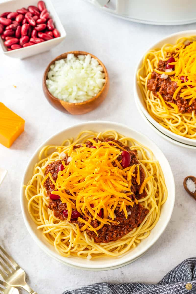 bowl of chili, spaghetti, beans, onion, and cheese