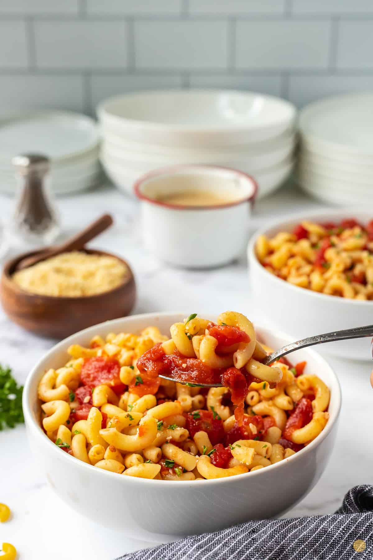 bowl of macaroni and tomatoes and a spoon