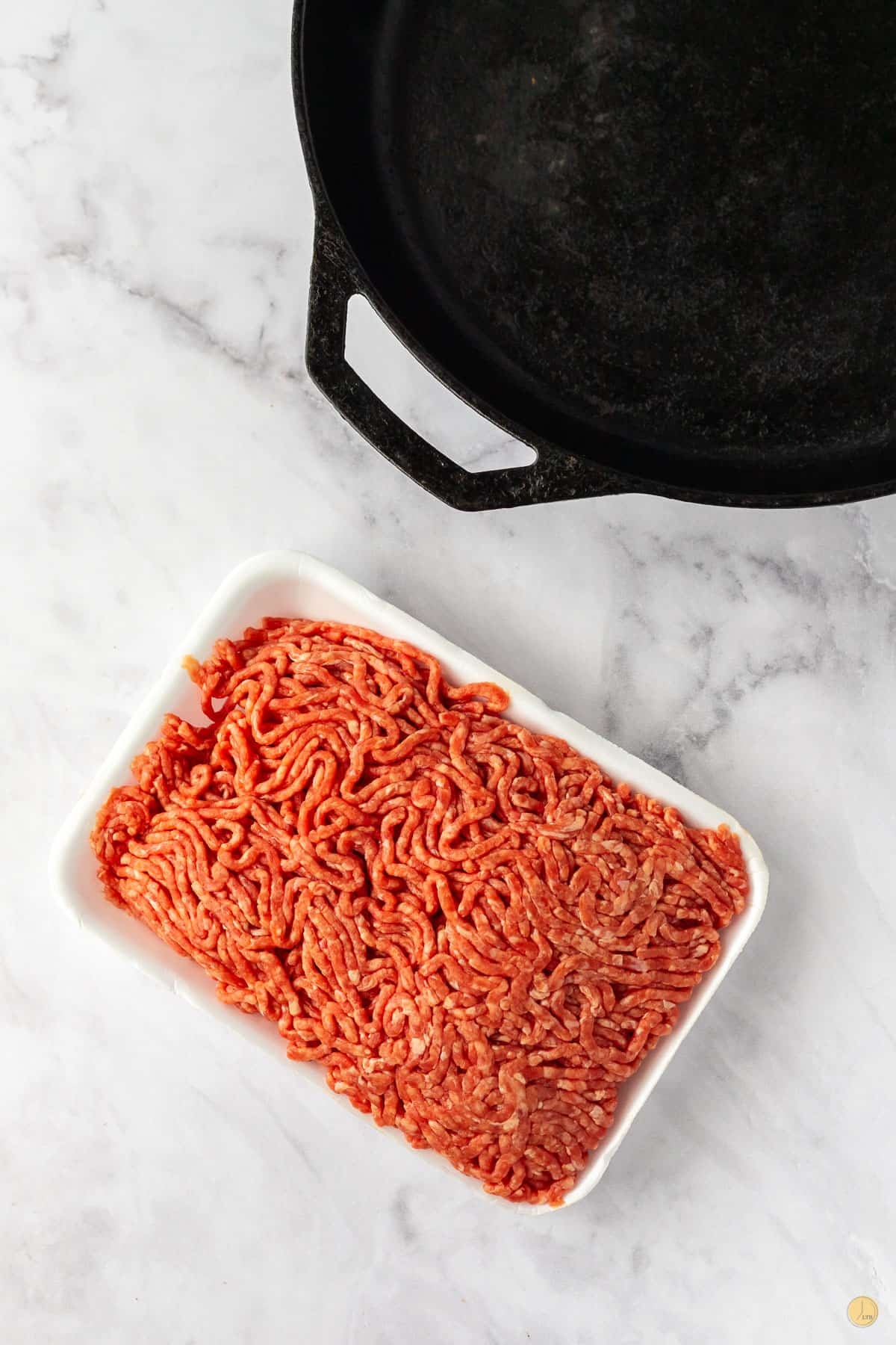 uncooked ground beef and a skillet