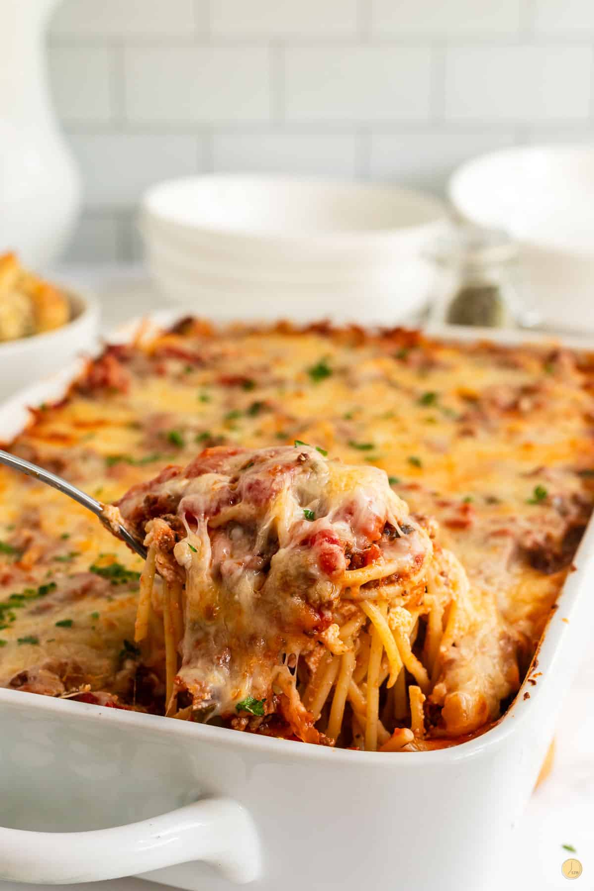 scoop of southern baked spaghetti in a white casserole dip